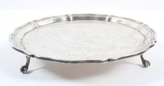 A small silver salver, with shaped edge, raised on three ball and claw feet, Birmingham 1938,