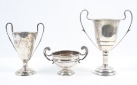 A silver two handled trophy, of traditional form, on a trumpet foot, with ribbon reed decoration,