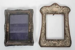 A wood backed silver photograph frame, of shaped form, decorated with scrolling foliates,
