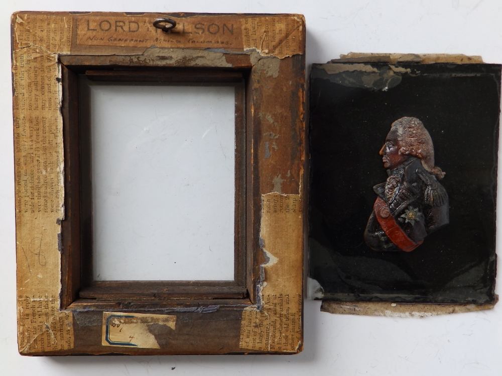 """Lot 64 - A reproduction relief moulded wax portrait of Nelson on glass panel in maple frame, 7"""" overall."""
