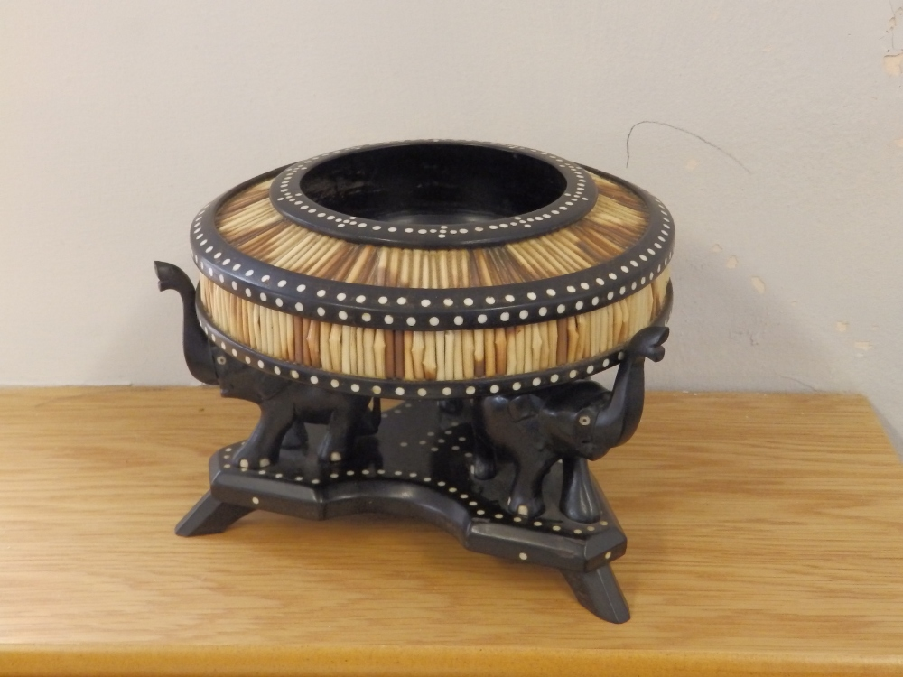 Lot 42 - A circular quillwork bowl on carved elephant stand.