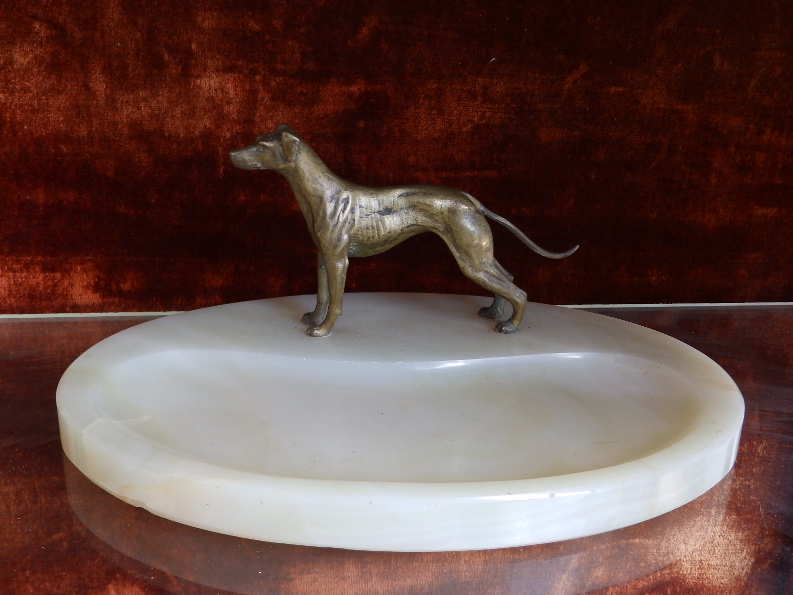 """Lot 98 - An oval green onyx desk stand mounted with a small gilt brass study of a dog, 10"""" across base,"""