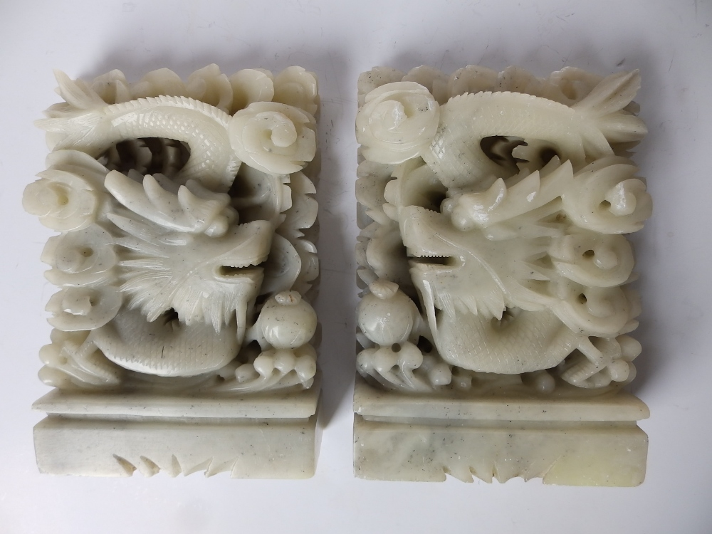 """Lot 63 - A pair of Chinese celadon soapstone dragon bookends, 7"""" high."""