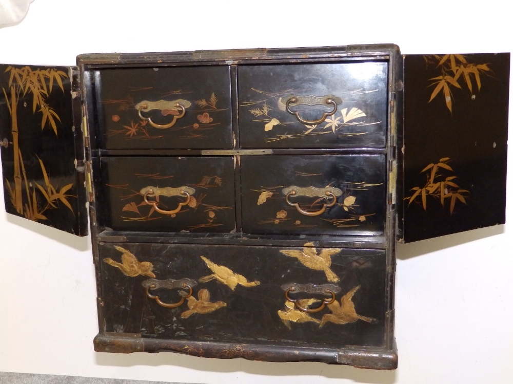 Lot 76 - A late 19thC Japanese lacquered table cabinet decorated overall with gilt birds against a self-