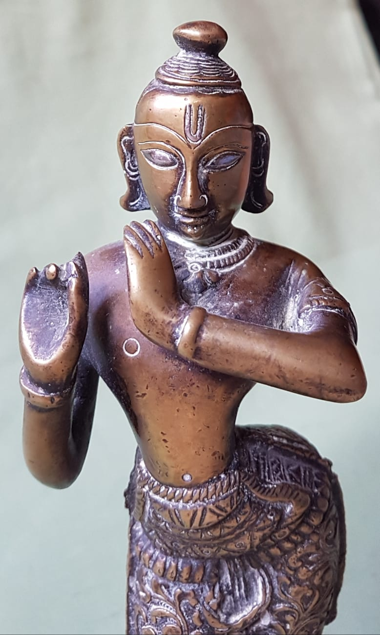"Lot 57 - An antique Indian brass figure, the eyes and forehead inlaid with silver, 9"" high."