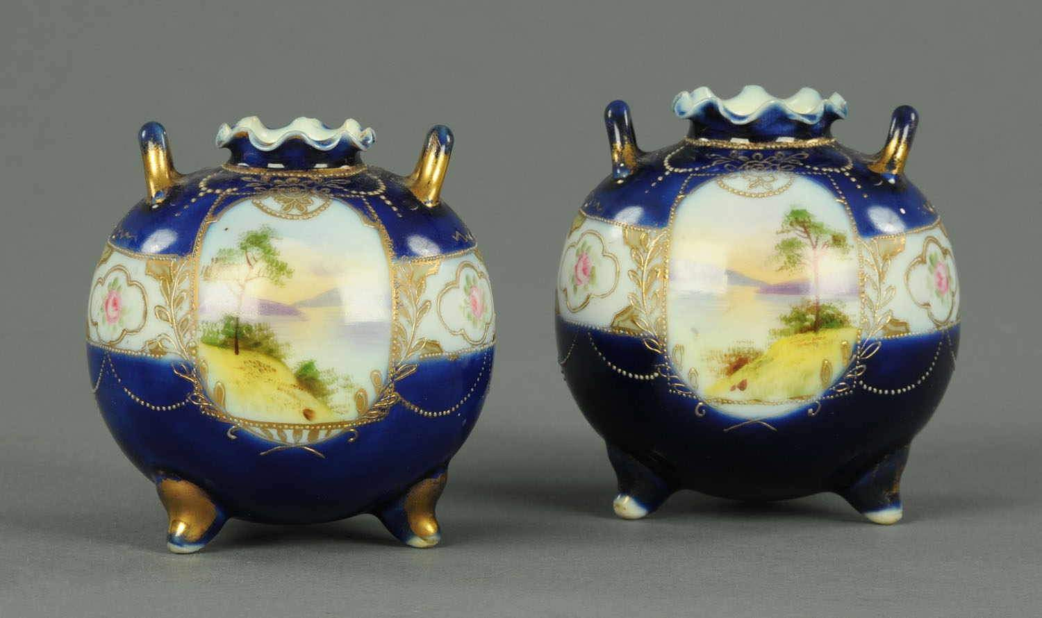 Lot 29 - A pair of Noritake squat vases, hand painted with landscapes and roses, printed marks to base.