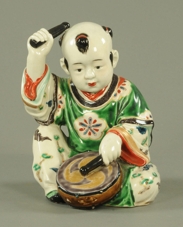 Lot 47 - A Japanese Kutani Karako drummer boy, Taisho period, modelled seated,