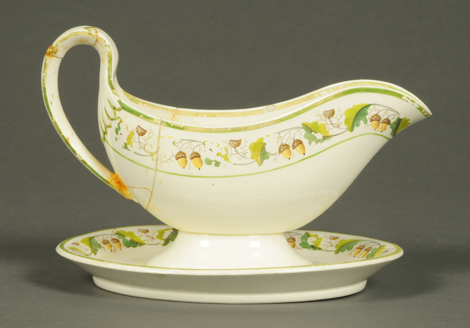 Lot 22 - A Davenport creamware sauce boat and stand, decorated with oak leaves and acorns, Patent Number 442.