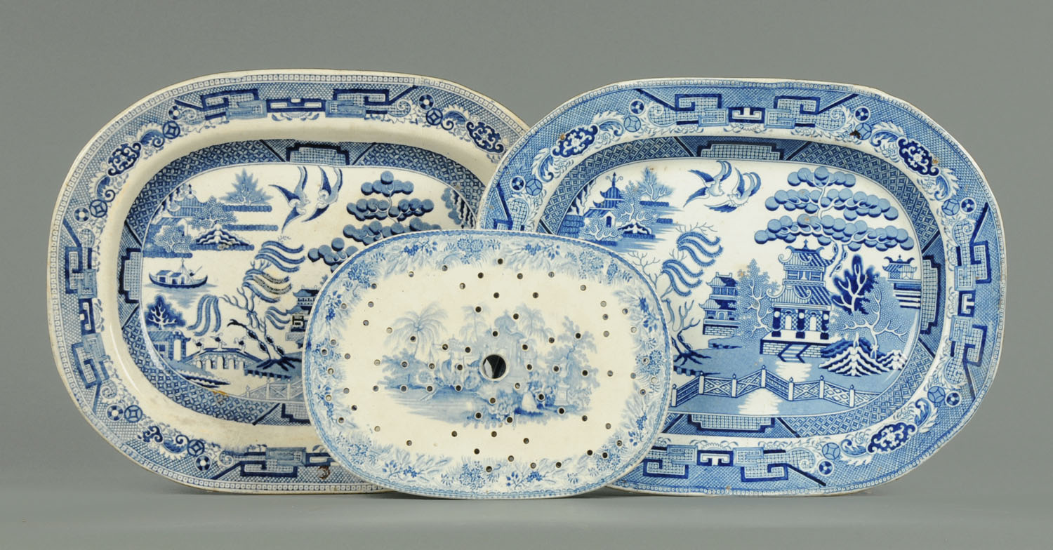 Lot 31 - Two large willow pattern blue and white transfer printed ashettes, together with a draining dish.