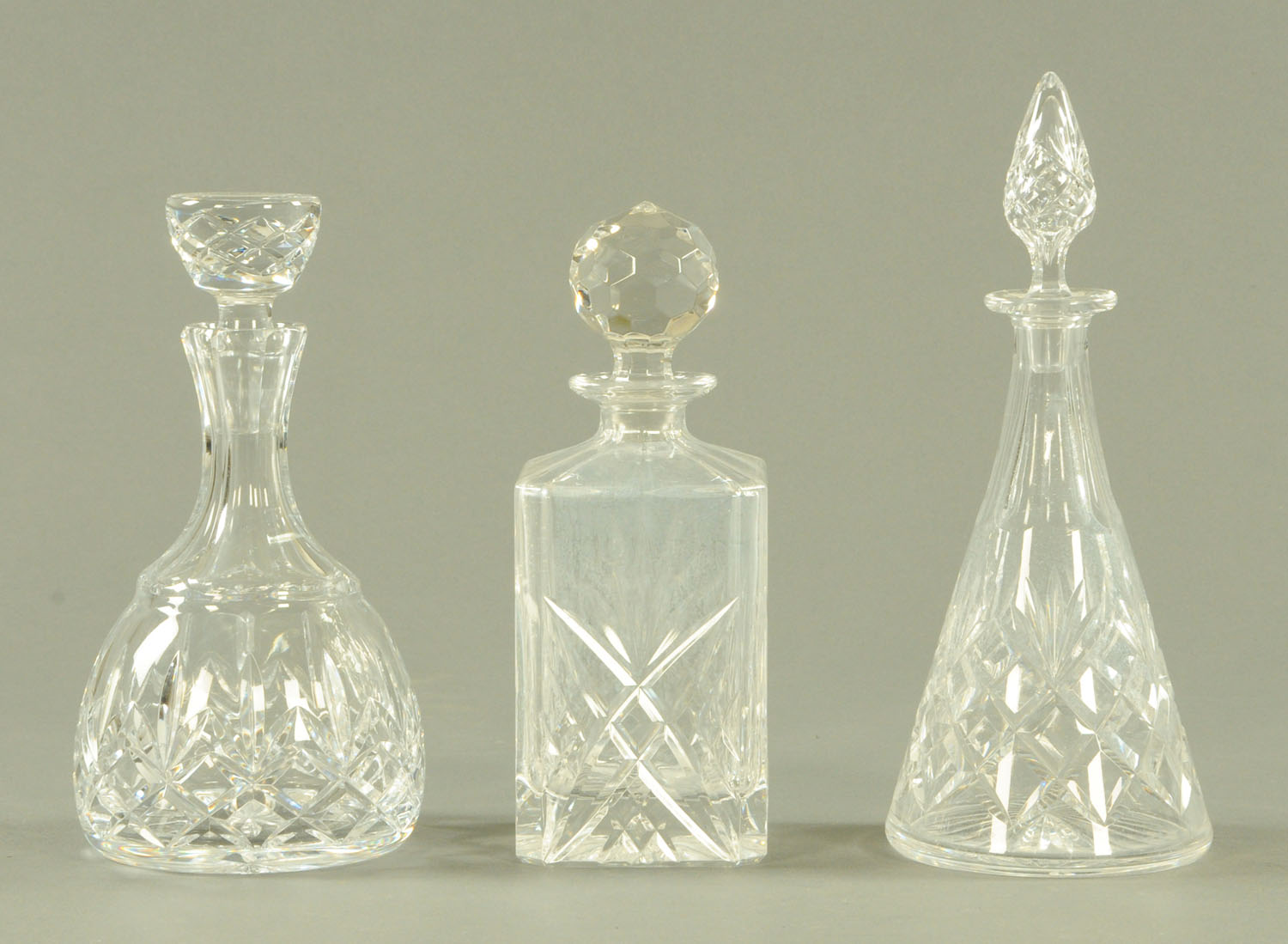 Lot 60 - Three cut glass decanters, each with stopper. Tallest 30 cm.