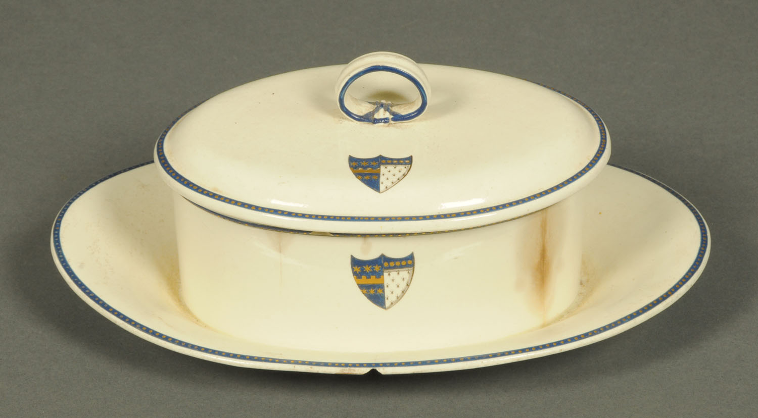 Lot 19 - A Wedgwood creamware butter dish and cover, decorated with an armorial shield. Length 22 cm.