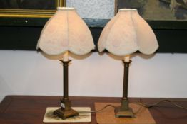 Two brass table lamps with cream and purple floral shades,