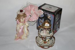 A modern plastic musical carrousel, 30 cm high, a plastic doll holding and parasol,