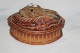 A 19th century pottery oval hare pie dish, the lid model with hares heads with glass eyes.