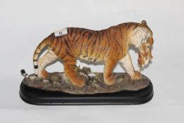 An Academy resin figure of a tiger and cub on wooden effect plinth, 23 cm high.