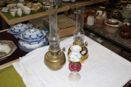 Two brass table oil lamps with chimneys, each 45 cm high including the chimneys,