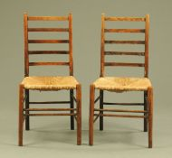 A pair of 19th century oak ladder back chairs with rush seats raised on turned legs.