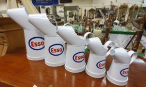 A graduated set of five modern Esso oil cans