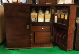 A Victorian mahogany apothecary's cabinet the two doors each fitted with eight bottle compartments
