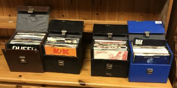 A collection of six singles cases and contents of various 45 rpm single records by Queen, Rainbow,