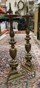 A pair of brass ecclesiastical style pricket candlesticks on turned and triangular form columns