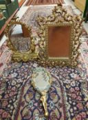 A gilded metal framed easel mirror with foliate decoration in the Rococo style,