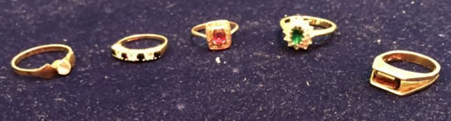 A collection of five gold stone set rings,