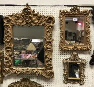 A small Rococo style carved giltwood framed wall mirror with scrolling acanthus decoration and two