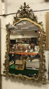 A gilt framed wall mirror with scrolling foliate decoration in the Rococo taste