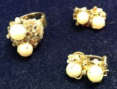 An unmarked yellow metal mid 20th Century pearl and stone set ring with stylised floral decoration