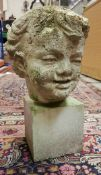 A carved white stone head of a young child, weathered,