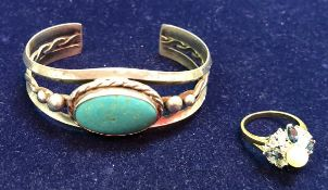 A yellow metal stone and pearl set dress ring together with a silver bangle with turquoise stone