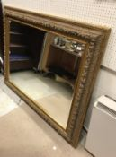 A large modern gilt framed wall mirror with scrolling foliate decoration