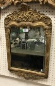 A circa 1700 carved giltwood and gesso framed wall mirror in the Rococo style
