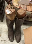 A pair of brown leather riding boots, together with a brown leather whip,