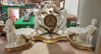 A 19th Century Moore Brothers clock garniture as two cherubs with floral decoration,