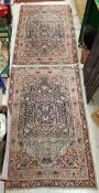 A pair of Kirman rugs with centre medallions on a deep blue ground within a red and pink ground
