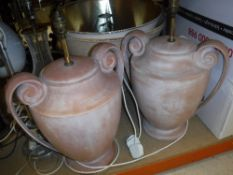 A pair of modern terracotta table lamps of scroll handled urn form.
