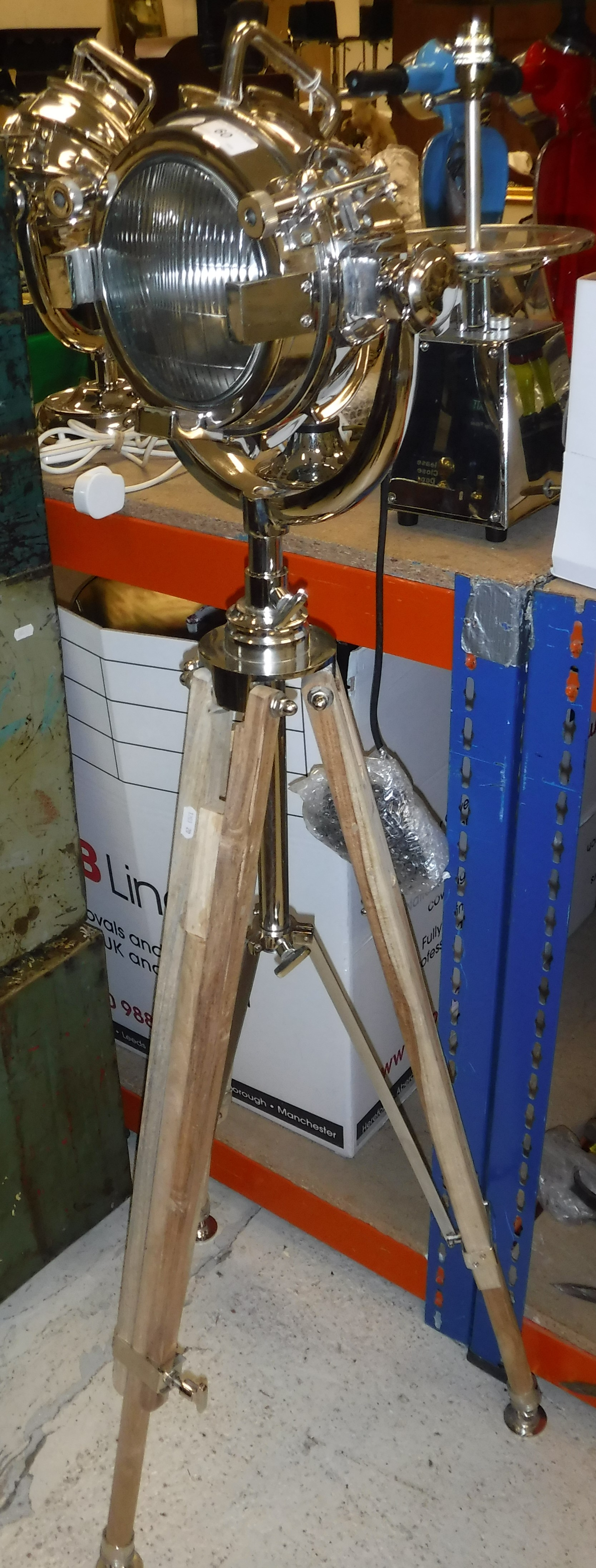 Lot 60 - A polished metal search light type lamp on an adjustable tripod base.