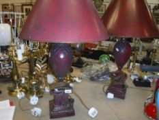 A pair of Regency style patinated red lacquered table lamps on plinth bases