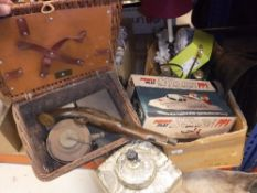 A coracle wicker picnic set containing kettle and burner, sandwich tin and further tin,