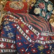 A box containing four various needlework scatter cushions, a carpet scatter cushion,