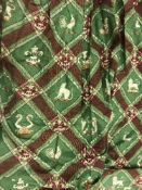 A pair of lined curtains with lattice style design with stags, lions, etc, on a green ground,