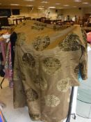 Two boxes of assorted textiles to include an olive green silk Chinese robe, a black velvet cape,