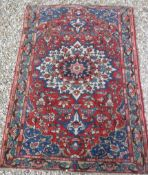 A Caucasian rug with central flower decorated star burst centre medallion on a floral decorated red