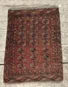 A Bokhara Tekke rug with all over elephant foot medallions on a red ground,
