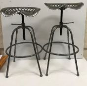 A pair of silver painted iron tractor seat stools