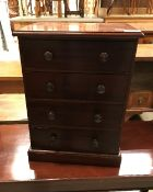 A miniature mahogany chest of 4 long dra