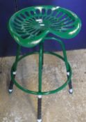"""A pair of green painted cast iron """"tractor seat"""" stools"""