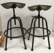 """A pair of iron tractor seat stools, the seats inscribed """"Wm Doyle & Co."""